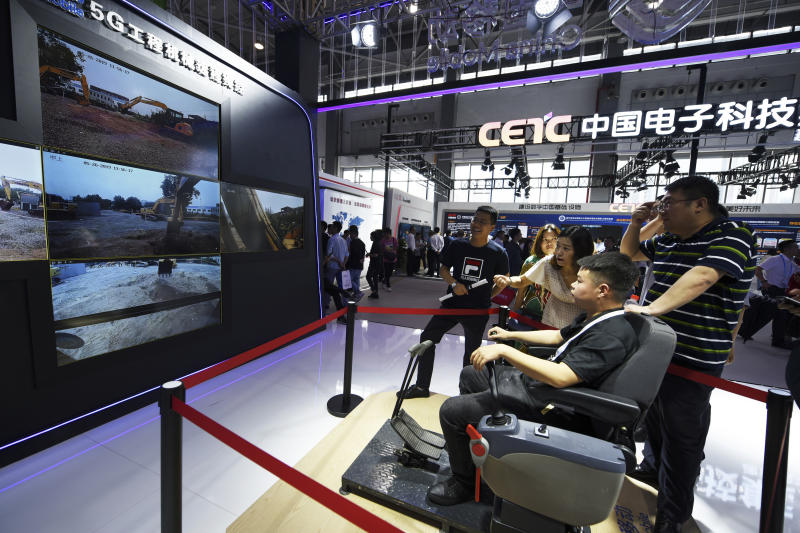 In this Sunday, May 26, 2019, photo released by Xinhua News Agency, a visitor operates an excavator which is shown on the TV screens by a remote control system via 5G technology at the China International Big Data Industry Expo 2019 in Guiyang, southwest China's Guizhou Province. China's latest media broadside in its trade war with the U.S. features an unlikely star: Trevor Noah of the Daily Show. The state broadcaster CCTV ran part of a segment from the show on Chinese equipment maker Huawei's dominance in 5G mobile technology in its lunchtime news show Monday, May 27. (Yang Wenbin/Xinhua via AP)