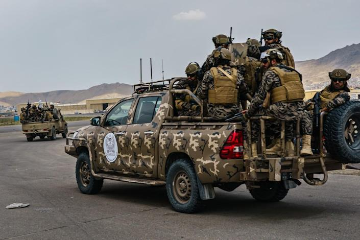 Taliban fighters ride in camouflage pickup trucks
