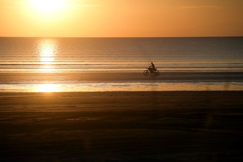 A local rides a dirt bike at Gunn Point Beach on the outskirts of Darwin, Friday, May 1, 2020. Northern Territory becomes the first state to ease COVID-19 restrictions.