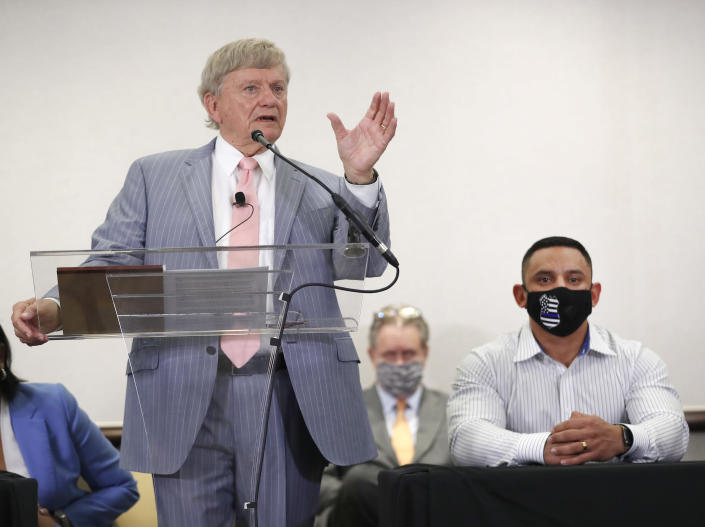 Houston Police officer Felipe Gallegos, right, listens as lawyer Rusty Hardin speaks during a press conference at Hilton Americas, Tuesday, Jan. 26, 2021, in Houston. Gallegos has been charged with murder and is among additional officers who have been indicted as part of an ongoing investigation into a Houston Police Department narcotics unit following a deadly 2019 drug raid, prosecutors announced Monday. (Karen Warren/Houston Chronicle via AP)