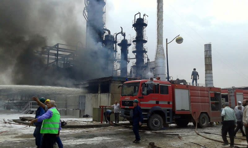 Firefighters try to put out a fire in main Homs refinery