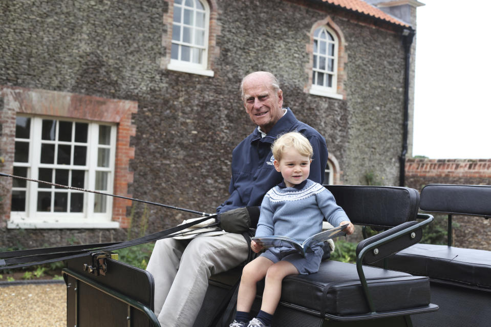 In this undated handout photo provided by the Duke and Duchess of Cambridge, Britain's Prince Philip sits with his great-grandson Prince George in England. Prince Philip, the irascible and tough-minded husband of Queen Elizabeth II who spent more than seven decades supporting his wife in a role that mostly defined his life, died on Friday, April 9, 2021. (Duke and Duchess of Cambridge via AP)