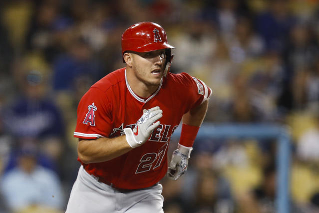 FILE - In this March 27, 2018, file photo, Los Angeles Angels' Mike Trout runs to first base after hitting a single during the third inning of an exhibition baseball game against the Los Angeles Dodgers, in Los Angeles. Tune into any game these days and you're bound to see hitters wearing helmets with a seven-inch piece of plastic _ the C-Flap _ curving around their cheek and jaw. (AP Photo/Jae C. Hong, FIle)