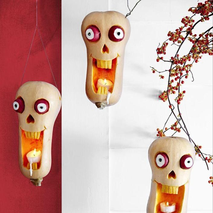 """<p>Suspend a trio of these haunted heads from the front porch. </p><ol><li>Use pumpkin carving tools to create a gaping mouth, nose and teeth in an upside-down butternut squash, then secure radish eyes with toothpicks. </li><li>With highlighter, draw tall rectangle mouth, teeth and smile lines on butternut squash. Carve mouth and lines, then etch skin off teeth with linoleum cutter. Hollow out inside of mouth only. </li><li>Carve upside-down heart for nose. </li><li>Cut eye sockets with top of knife tilted toward the pumpkin. </li><li>Slice an end off of 2 radishes and push in black beans for pupils, then add 2 toothpicks to the back of each and push into sockets. </li><li>Poke deep hole in either side of squash at top with an awl. </li><li>Tape a length of <a href=""""https://www.amazon.com/KastKing-Worlds-Premium-Monofilament-Yards/dp/B01N6ZU47X/ref=sr_1_1_sspa?keywords=Monofilament&qid=1563288124&s=sporting-goods&sr=1-1-spons&psc=1&tag=syn-yahoo-20&ascsubtag=%5Bartid%7C10070.g.2488%5Bsrc%7Cyahoo-us"""" rel=""""nofollow noopener"""" target=""""_blank"""" data-ylk=""""slk:monofilament"""" class=""""link rapid-noclick-resp"""">monofilament</a> to wood skewer and thread through holes; discard skewer. Knot ends of monofilament together; use loop to hang.</li></ol><p><strong>What You'll Need: </strong><a href=""""https://www.amazon.com/KastKing-Worlds-Premium-Monofilament-Yards/dp/B01N6ZU47X/ref=sr_1_1_sspa?keywords=Monofilament&qid=1563288124&s=sporting-goods&sr=1-1-spons&psc=1&tag=syn-yahoo-20&ascsubtag=%5Bartid%7C10070.g.2488%5Bsrc%7Cyahoo-us"""" rel=""""nofollow noopener"""" target=""""_blank"""" data-ylk=""""slk:Monofilament"""" class=""""link rapid-noclick-resp"""">Monofilament</a> ($9, Amazon) </p>"""