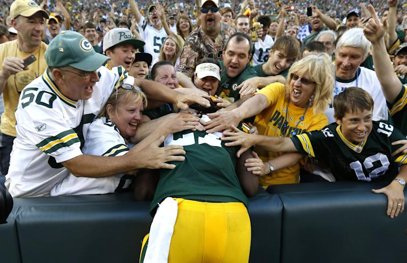 Green Bay Packers running back Eddie Lacy, center, leaps into the crowd after rushing for a touchdown against the Oakland Raiders during the first half of an NFL preseason football game Friday, Aug. 22, 2014, in Green Bay, Wis