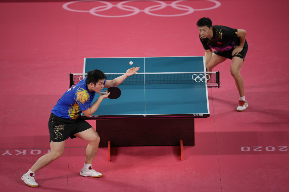 Fan Zhendong of China, left, prepares to serve to Ma Long of China during a gold medal match of the table tennis men's singles against at the 2020 Summer Olympics, Friday, July 30, 2021, in Tokyo. (AP Photo/Kin Cheung)
