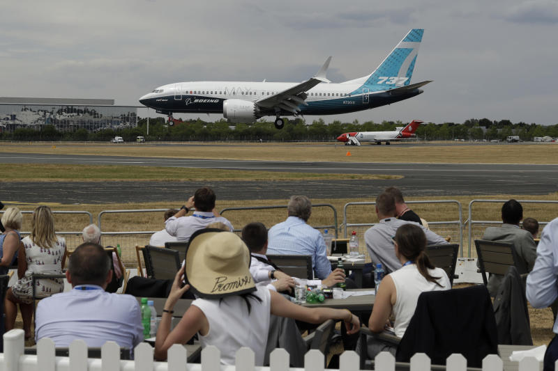 Spectators watch a Boeing 737 land after a flying display at the Farnborough Airshow in Farnborough, England, Monday, July 16, 2018. (AP Photo/Matt Dunham)
