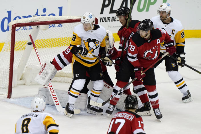 New Jersey Devils and Pittsburgh Penguins players watch as a goal by Pittsburgh Penguins right wing Bryan Rust goes past New Jersey Devils goaltender Mackenzie Blackwood (29) during the second period of an NHL hockey game, Sunday, April 11, 2021, in Newark, N.J. (AP Photo/Kathy Willens)