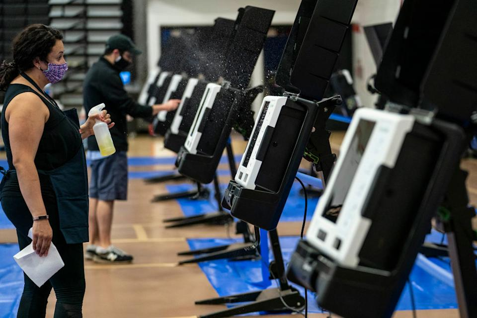 A volunteer disinfects a voting machine at an early voting centre in Washington, DC. Source: Getty