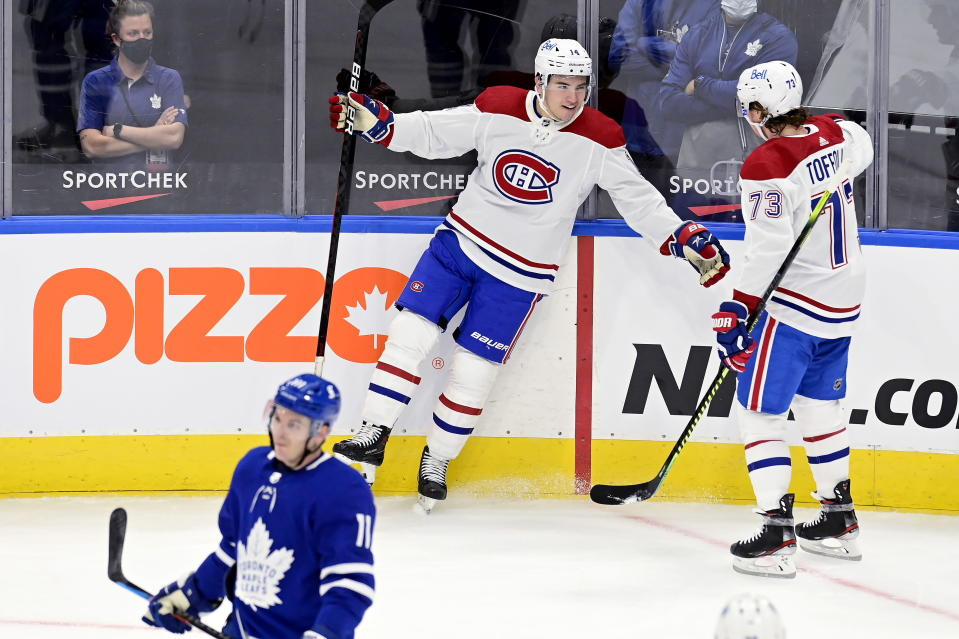 Montreal Canadiens center Nick Suzuki (14) celebrates a goal with teammate Tyler Toffoli (73) as Toronto Maple Leafs left wing Zach Hyman (11) skates by during the first period of an NHL hockey game Wednesday, Jan. 13, 2021 in Toronto. (Frank Gunn/The Canadian Press via AP)