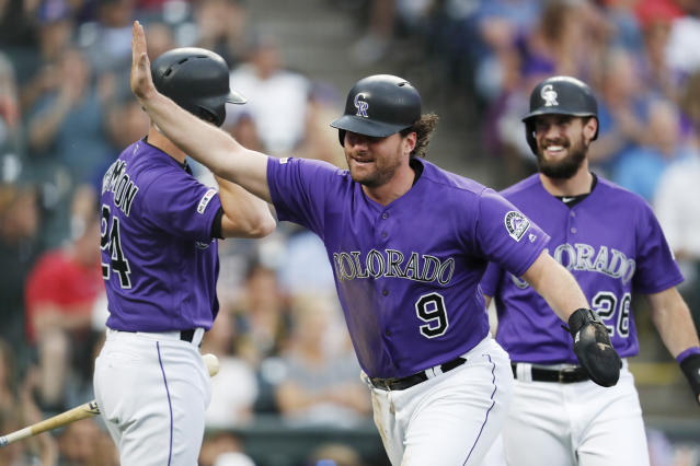 Colorado Rockies' Daniel Murphy, front, celebrates after scoring on a double by Ian Desmond, next to Ryan McMahon, back left, and David Dahl during the first inning of a baseball game against the San Diego Padres on Thursday, June 13, 2019, in Denver. (AP Photo/David Zalubowski)