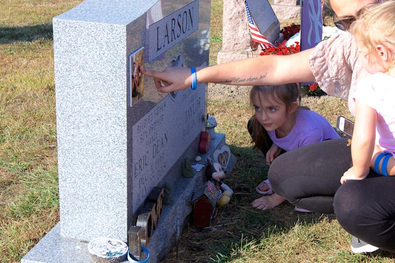 Taylor Bromberg, 26, visited the grave of her fiancé Eric Larson with her daughters, Adriana Nicole, 5, and Mikayla Grace, 2. Larson was killed by a suspect fleeing police.