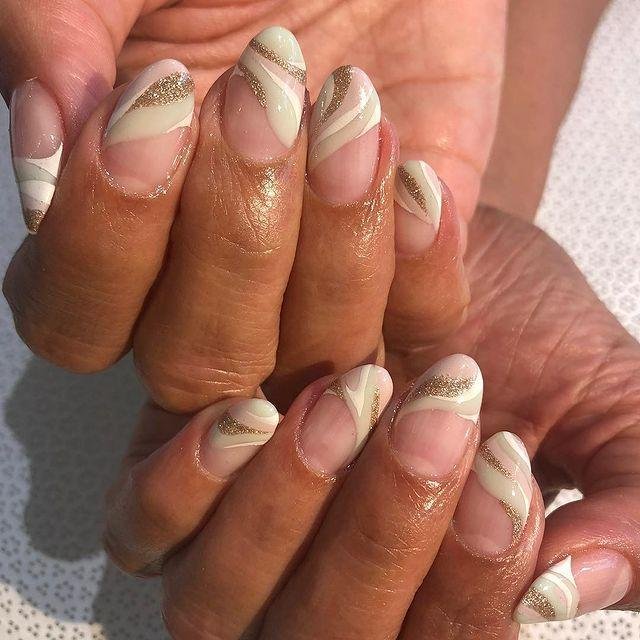 """<p>Waves of cream, pink and rose gold glitter compliment one another over a neutral/clear base. Definitely one to book an appointment for.</p><p><a href=""""https://www.instagram.com/p/Bj-DszcHYKF/"""" rel=""""nofollow noopener"""" target=""""_blank"""" data-ylk=""""slk:See the original post on Instagram"""" class=""""link rapid-noclick-resp"""">See the original post on Instagram</a></p>"""