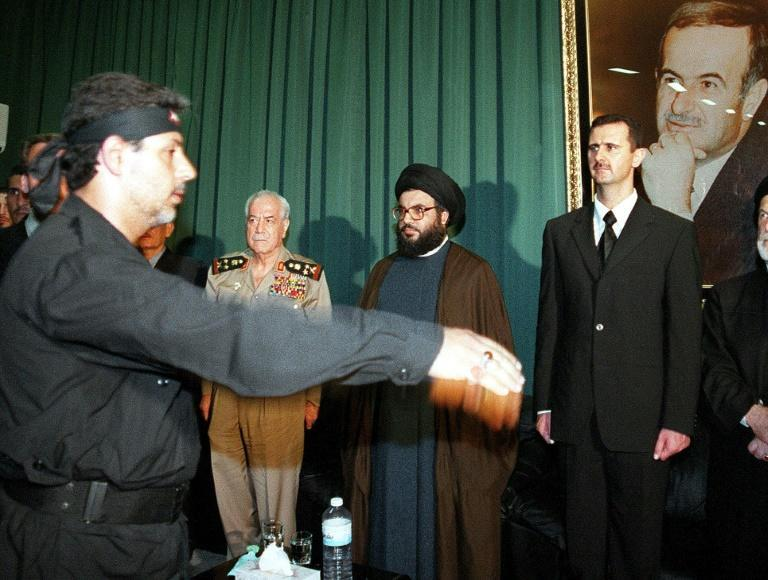In this file photo taken on June 16, 2000, days after the death of Hafez al-Assad, the leader of Lebanese Shiite group Hezbollah, Hassan Nasrallah (C), is seen flanked by Bashar al-Assad (R) and Syrian Defence Minister Mustafa Tlass in Qardaha, Syria