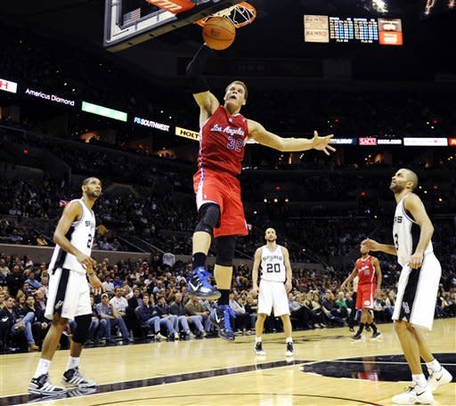 Los Angeles Clippers forward Blake Griffin goes up for an uncontested dunk between San Antonio Spurs' Tim Duncan (21), Manu Ginobili, of Argentina, (20) and Tony Parker, of France, (9) during the first half of an NBA basketball game in San Antonio, Wednesday, Dec. 28, 2011. (AP Photo/Bahram Mark Sobhani)
