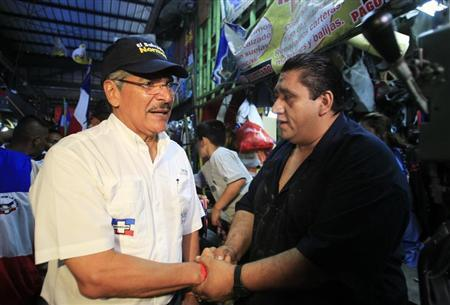Quijano, presidential candidate from the conservative Nationalist Republican Alliance party, shakes hands with a man at a local market in La Libertad