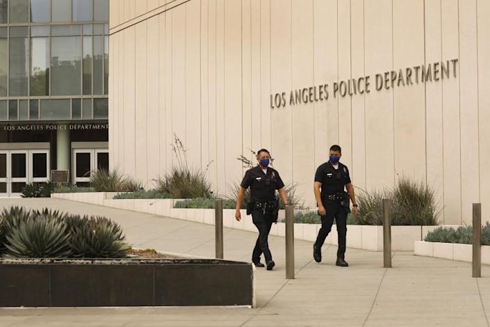"""Police officers walk outside the LAPD's headquarters in downtown Los Angeles on July 1. <span class=""""copyright"""">(Los Angeles Times)</span>"""