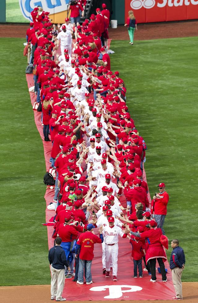 Philadelphia Phillies' manager Ryne Sandberg leads his team from centerfield while surrounded by fans for an opening day baseball game between the Milwaukee Brewers and Philadelphia Phillies in Philadelphia, Tuesday, April 8, 2014. (AP Photo/Chris Szagola)