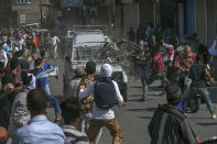 CORRECTS AGE - FILE - In this Friday, June 1, 2018, file photo, Kashmiri Protesters attack an Indian paramilitary vehicle in Srinagar, Indian controlled Kashmir. The death of top separatist leader Syed Ali Geelani on Sept. 1, 2021, in disputed Kashmir and the ensuing crackdown on public movement and communications by Indian authorities have highlighted the turmoil seething just below the surface in the region. Soon after the 91-year-old's death late Wednesday, authorities quickly clamped down, blocking internet and mobile phone services and restricting public movement out of fear of anti-India protests. (AP Photo/Dar Yasin, File)