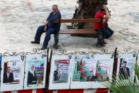Men sit near parliamentary election campaign posters in Algiers