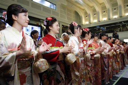 Women, dressed in ceremonial kimonos, clap during the New Year opening ceremony at the TSE, held to wish for the success of Japan's stock market, in Tokyo