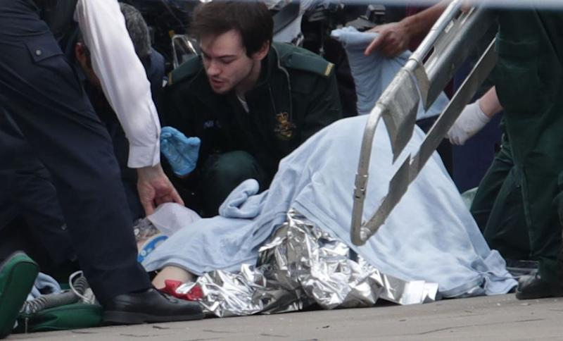 An injured person is treated at the sight of the London terror attack. Photo: AAP