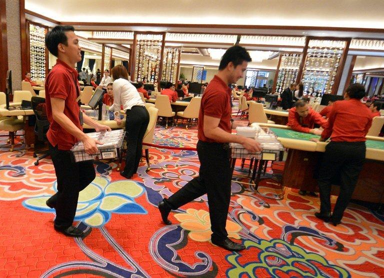 Employees of Solaire Resorts and casino, carry gaming cards during a dry run at the casino, in Manila, on March 14, 2013, ahead of its Saturday opening. Solaire Manila Resorts is the first of four huge entertainment venues slated to rise on reclaimed land on Manila Bay that industry and government officials hope will draw millions of newly well-off Asian visitors