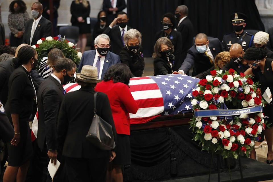 <p>Members of Congress paid their respects by reaching out to touch Lewis's casket. </p>