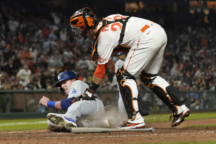San Francisco Giants catcher Buster Posey, top, tags out Los Angeles Dodgers' Luke Raley at home during the eighth inning of a baseball game in San Francisco, Tuesday, July 27, 2021. (AP Photo/Jeff Chiu)