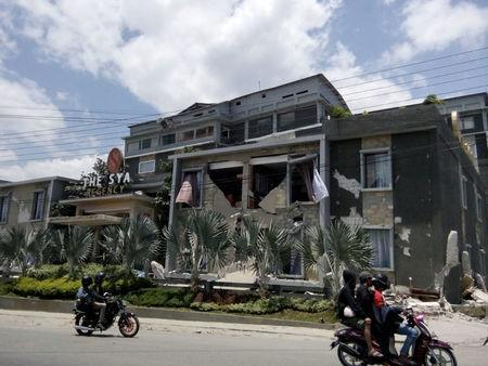 Young people drive a motorcycle near damaged house after earthquake hit in Palu, Indonesia September 29, 2018. REUTERS/Stringer