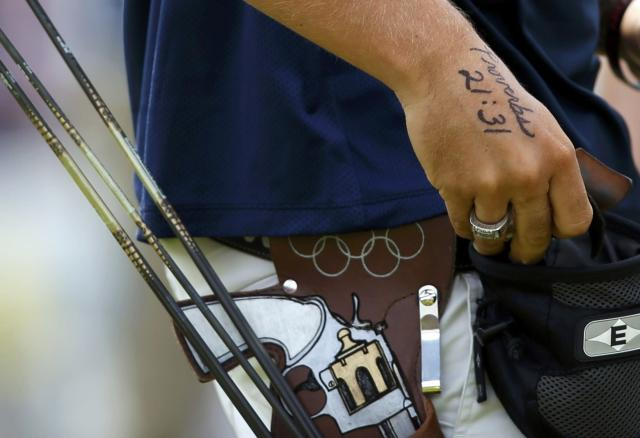 A tattoo of a Bible verse is seen on the hands of Brady Ellison of the U.S. as he prepares to take aim during the men's archery team quaterfinals at the Lords Cricket Ground during the London 2012 Olympics Games July 28, 2012. REUTERS/Suhaib Salem (BRITAIN - Tags: SPORT OLYMPICS SPORT ARCHERY)