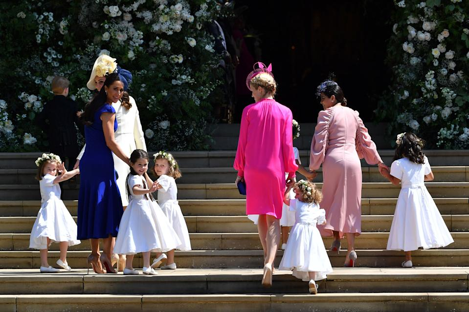 The Duchess of Cambridge and Meghan Markle's friend, Canadian fashion stylist Jessica Mulroney (second left) holds bridesmaids hands as they arrive for the wedding ceremony of Prince Harry to Meghan Markle at St. George's Chapel in Windsor Castle. (Photo by Ben Stansall/PA Images via Getty Images)