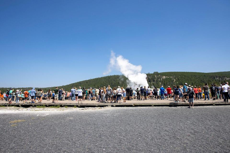 Hundreds of tourists gather on a boardwalk to watch Old Faithful Geyser erupt on July 14, 2021 at Yellowstone National Park, Wyoming.