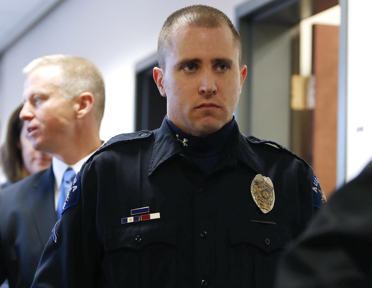 Aurora Police Officer Justin Grizzle leaves court after testifying at a preliminary hearing for James Holmes at the courthouse in Centennial, Colo., on Monday, Jan. 7, 2013. Investigators say Holmes opened fire during the midnight showing of the latest Batman movie on July 20, killing 12 people and wounding dozens. Grizzle fought to keep his composure during his testimony, in which he described people running from the theater, wounded people trying to crawl from the theater, and people uninjured helping those who had been injured. (AP Photo/Ed Andrieski)