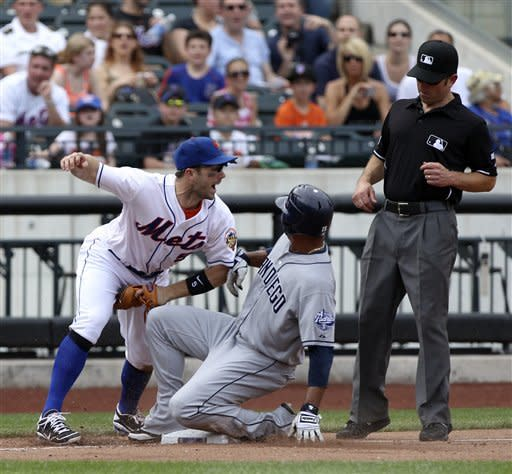 New York Mets third baseman David Wright, left, reacts as San Diego Padres' Jesus Guzman, center, is caught trying to steal third while umpire Chris Guccione, right, looks on during the seventh inning of the baseball game on Sunday, May 27, 2012, at Citi Field in New York. (AP Photo/Seth Wenig)
