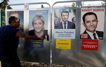 Sauveur, a member of the French National Front (FN) political party pastes a poster on a official billboard for French National Front (FN) political party leader Marine Le Pen near the posters of  Emmanuel Macron (C), head of the political movement En Marche! (Onwards !), and French Socialist party candidate Benoit Hamon (R) as part of the 2017 French presidential election campaign in Antibes, France, April 14, 2017.   REUTERS/Eric Gaillard