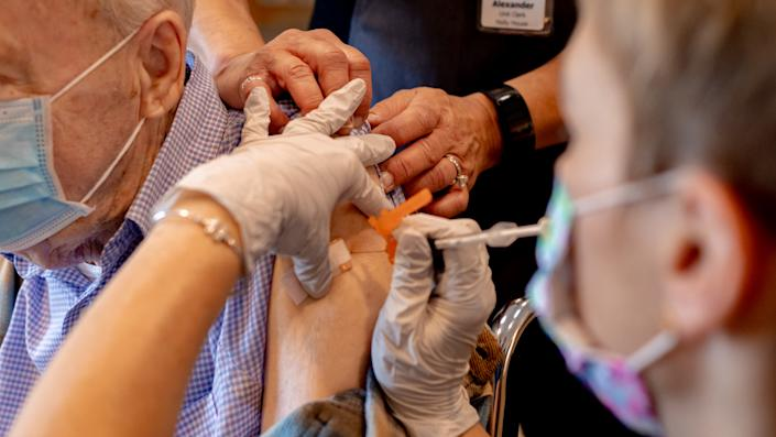 A health care worker administers a third dose of the Pfizer-BioNTech COVID-19 vaccine at a senior living facility in Worcester, Penn., in August.