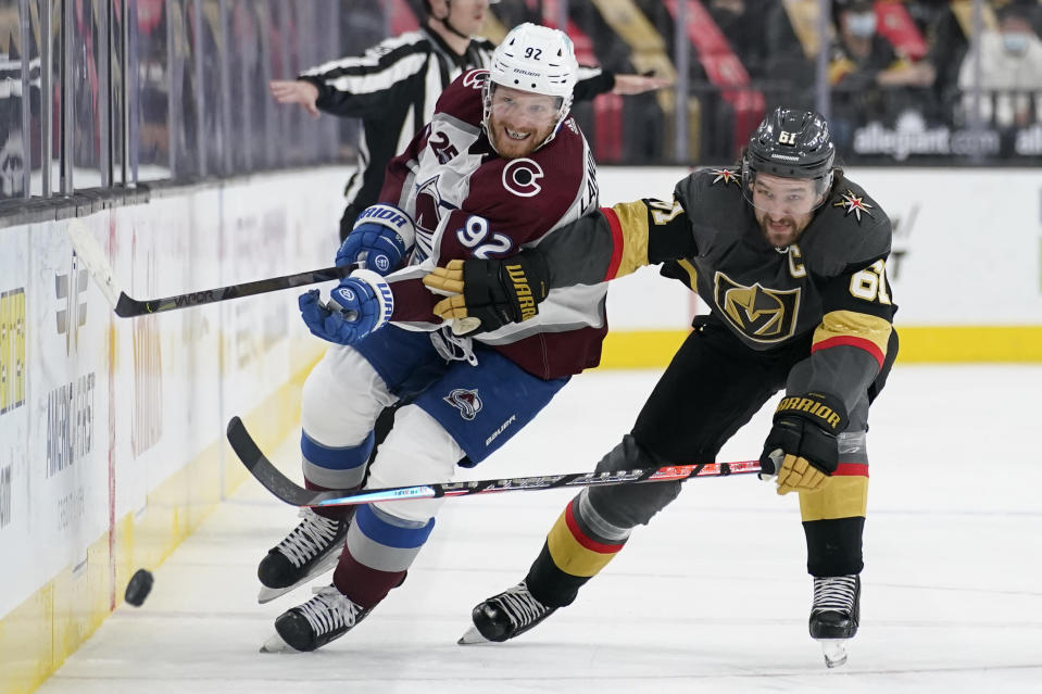 Vegas Golden Knights right wing Mark Stone (61) and Colorado Avalanche left wing Gabriel Landeskog (92) battle for the puck during the third period of an NHL hockey game Monday, May 10, 2021, in Las Vegas. (AP Photo/John Locher)