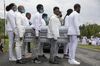 """Family including Iran """"Bang"""" Paylor, of Washington, far left, carry the casket of Paylor's mother, Joanne Paylor, 62, of southwest Washington, to a horse drawn hearse during her funeral at Cedar Hill Cemetery in Suitland-Silver Hill, Md., Sunday, May 3, 2020. Despite not having died from coronavirus, almost every aspect of her funeral has been impacted by the pandemic. (AP Photo/Jacquelyn Martin)"""