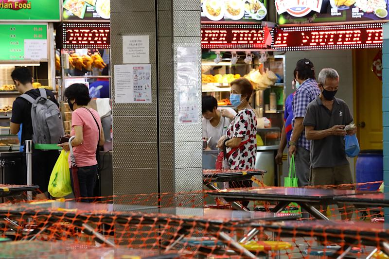 SINGAPORE - APRIL 08: People wearing protective masks queue to buy a takeway food at a hawker centre as dining areas are sealed off with nets as the government implements a take-away only policy to curb the spread of the coronavirus on April 8, 2020 in Singapore. Singapore government started closing non-essential workplaces and schools temporarily for a month from April 7 to contain the spread of coronavirus (COVID-19) infections. (Photo by Suhaimi Abdullah/Getty Images)