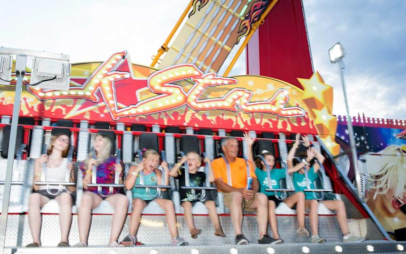 Fairgoers scream and shout as they are catapulted into the air. | Jason Bergman