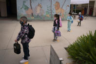Socially distanced kindergarten students wait for their parents to pick them up on the first day of in-person learning at Maurice Sendak Elementary School in Los Angeles, Tuesday, April 13, 2021. More than a year after the pandemic forced all of California's schools to close classroom doors, some of the state's largest school districts are slowly beginning to reopen this week for in-person instruction. (AP Photo/Jae C. Hong)