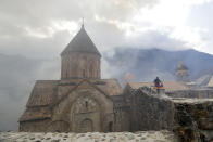 An Armenian man with an Armenian national flag, visits the 12th-13th century Orthodox Dadivank Monastery on the outskirts of Kalbajar, the separatist region of Nagorno-Karabakh, on Friday, Nov. 13, 2020. Under an agreement ending weeks of intense fighting over Nagorno-Karabakh, some Armenian-held territories, such as this area will pass to Azerbaijan. (AP Photo/Sergei Grits)