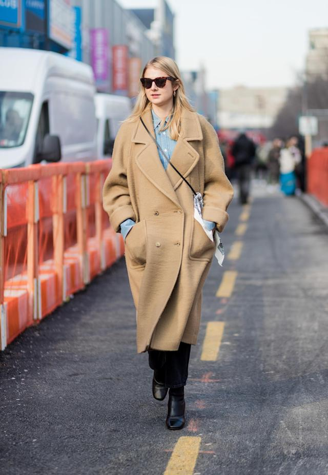 <p>This is a classic all-American look — an oversized tan coat with large lapels, layered over a chambray shirt and black jeans, and pulled together with a pair of leather boots. These are all staples you probably already have in your closet, for a look you can easily recreate. (Photo: Getty) </p>
