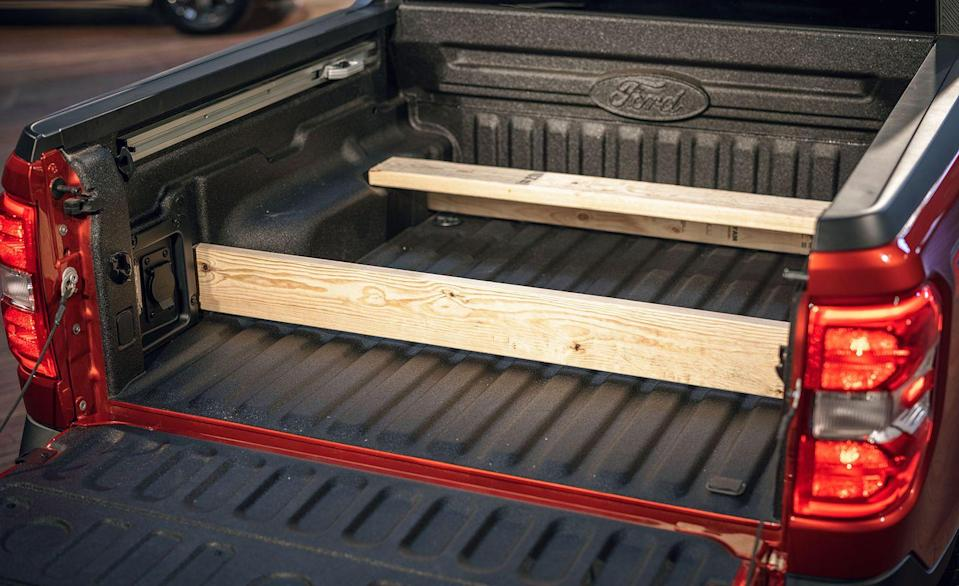 """<p>Every Ford Maverick comes with a 4.5-foot bed and a max payload of 1500 pounds. The floor extends to six feet with the tailgate down, which Ford says can support up to 18 sheets of 4x8-foot three-quarter-inch plywood. Both the cabin and the bed have a 110-volt 400-watt outlet for charging cordless power tools or powering a television. There are also plenty of tie-down hooks for securing cargo. Ford's Flexbed gives you a little more freedom when it comes to carrying the job around. The Flexbed has slots stamped into the bed which allow for 2x4s or 2x6s to be inserted, keeping items from sliding around or out of the bed entirely. (Wood planks sold separately.) Although the Maverick will have a longer bed than the Hyundai Santa Cruz compact pickup, it's at least 1.5-foot shorter than every mid-size pickup sold today, with the exception of the <a href=""""https://www.caranddriver.com/jeep/gladiator"""" rel=""""nofollow noopener"""" target=""""_blank"""" data-ylk=""""slk:Jeep Gladiator"""" class=""""link rapid-noclick-resp"""">Jeep Gladiator</a>'s five-foot bed. </p>"""