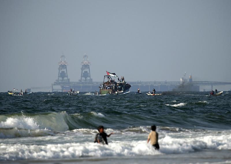 Palestinian boats participate in a protest against the more than a decade-long blockade of Gaza on August 11, 2018 with Israel's Rutenberg power station seen in the background (AFP Photo/MAHMUD HAMS)