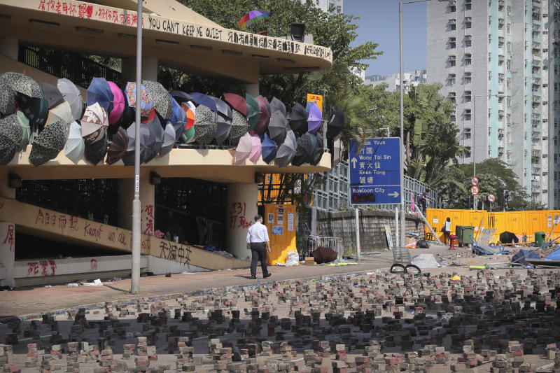 A man walks past barricades built by protesters at Hong Kong Baptist University in Hong Kong, Friday, Nov. 15, 2019. Protesters who have barricaded themselves in a Hong Kong university partially cleared a road they were blocking and demanded that the government commit to holding local elections on Nov. 24. (AP Photo/Kin Cheung)