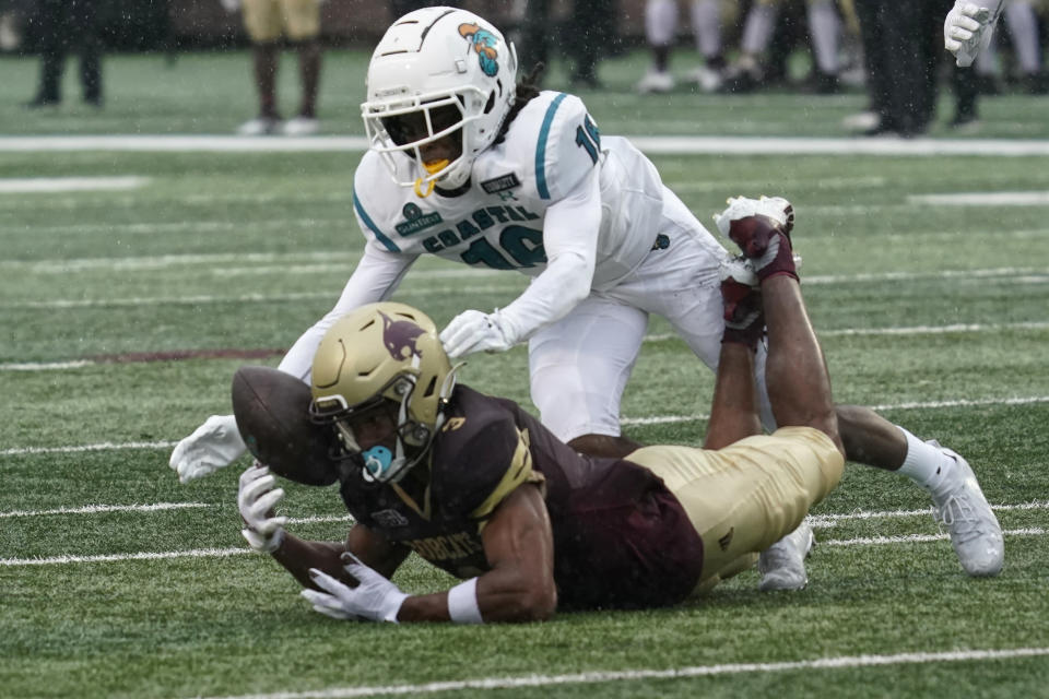 Coastal Carolina's Jordan Morris (16) reaches over Texas State's Jeremiah Haydel (3) after Haydel muffed a punt during the second half of an NCAA college football game in San Marcos, Texas, Saturday, Nov. 28, 2020. Texas State recovered the ball. (AP Photo/Chuck Burton)