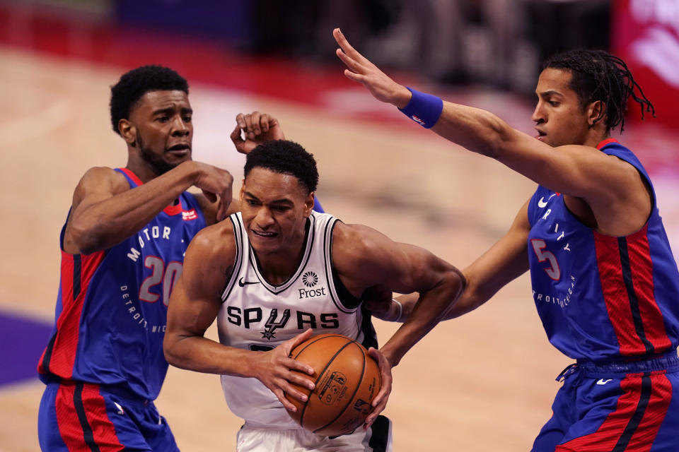 San Antonio Spurs guard Devin Vassell (24) drives between Detroit Pistons guard Josh Jackson (20) and guard Frank Jackson (5) during the second half of an NBA basketball game, Monday, March 15, 2021, in Detroit. (AP Photo/Carlos Osorio)