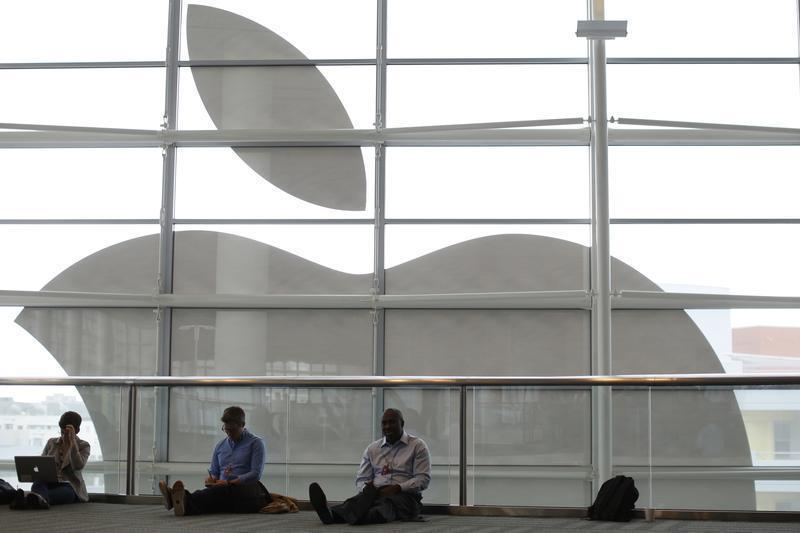 Attendees sit in front of an Apple logo at the WWDC 2013 in San Francisco
